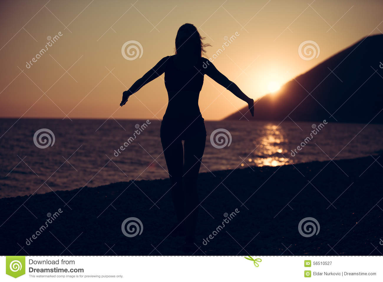 Carefree woman dancing in the sunset on the beach.Vacation vitality healthy living concept.Free woman enjoying freedom feeling hap
