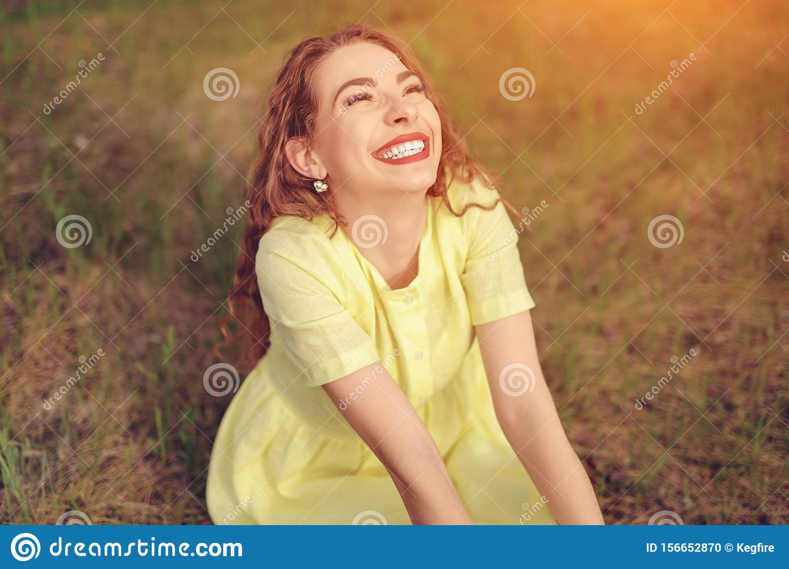 Carefree woman laughing sitting in field