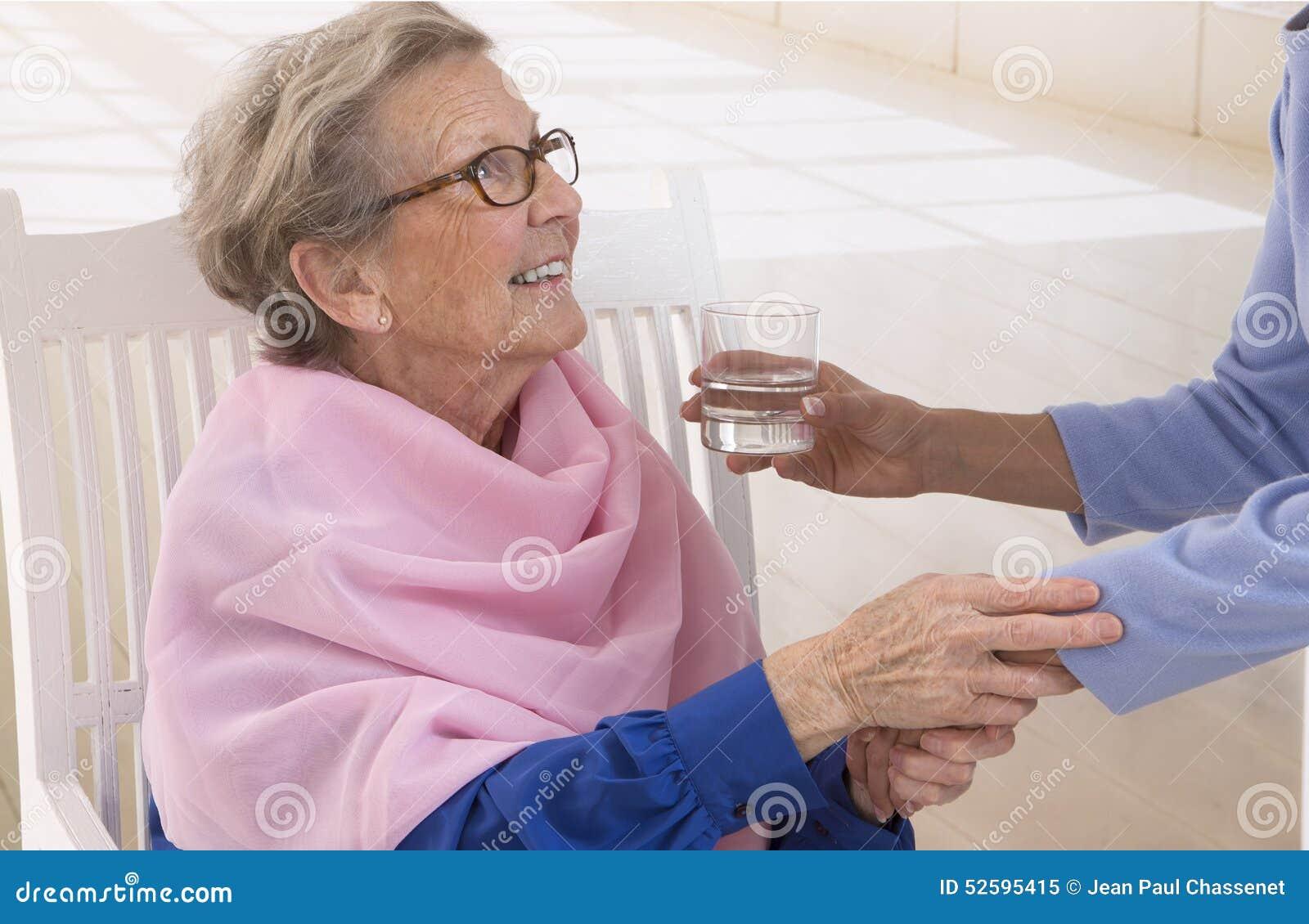 Caregiver που δίνει το ποτήρι του νερού σε μια κομψή ανώτερη γυναίκα