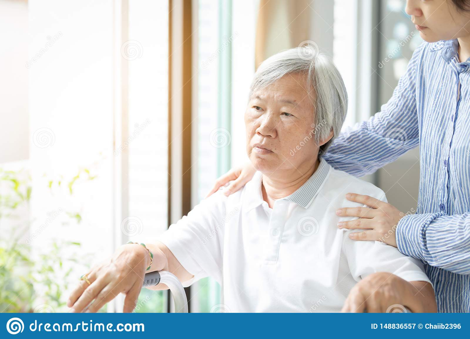 Caregiver asian daughter or young nurse standing behind the senior woman looking at window with hand on elder woman's shoulder,