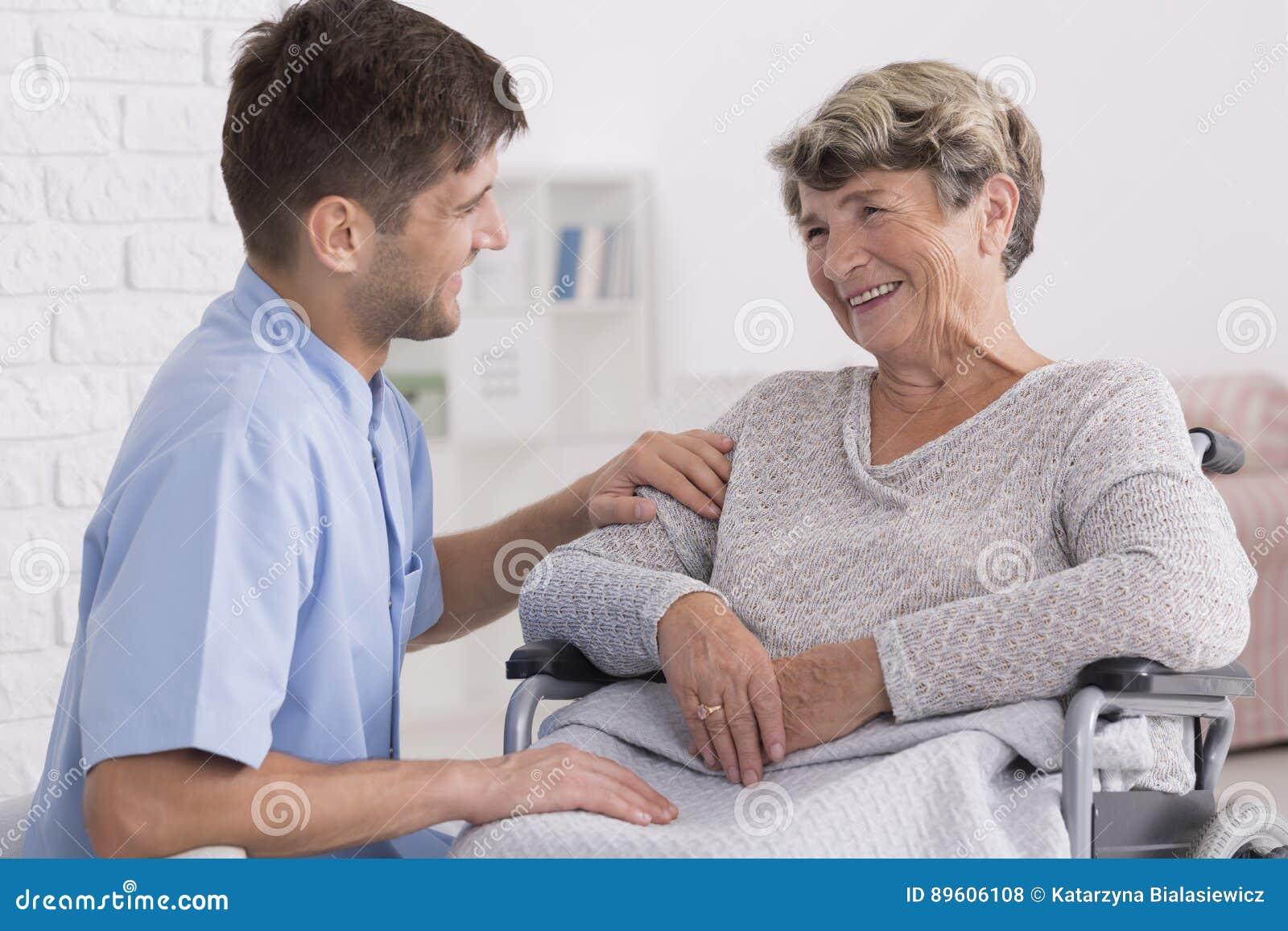 Caregiver comforting elderly woman