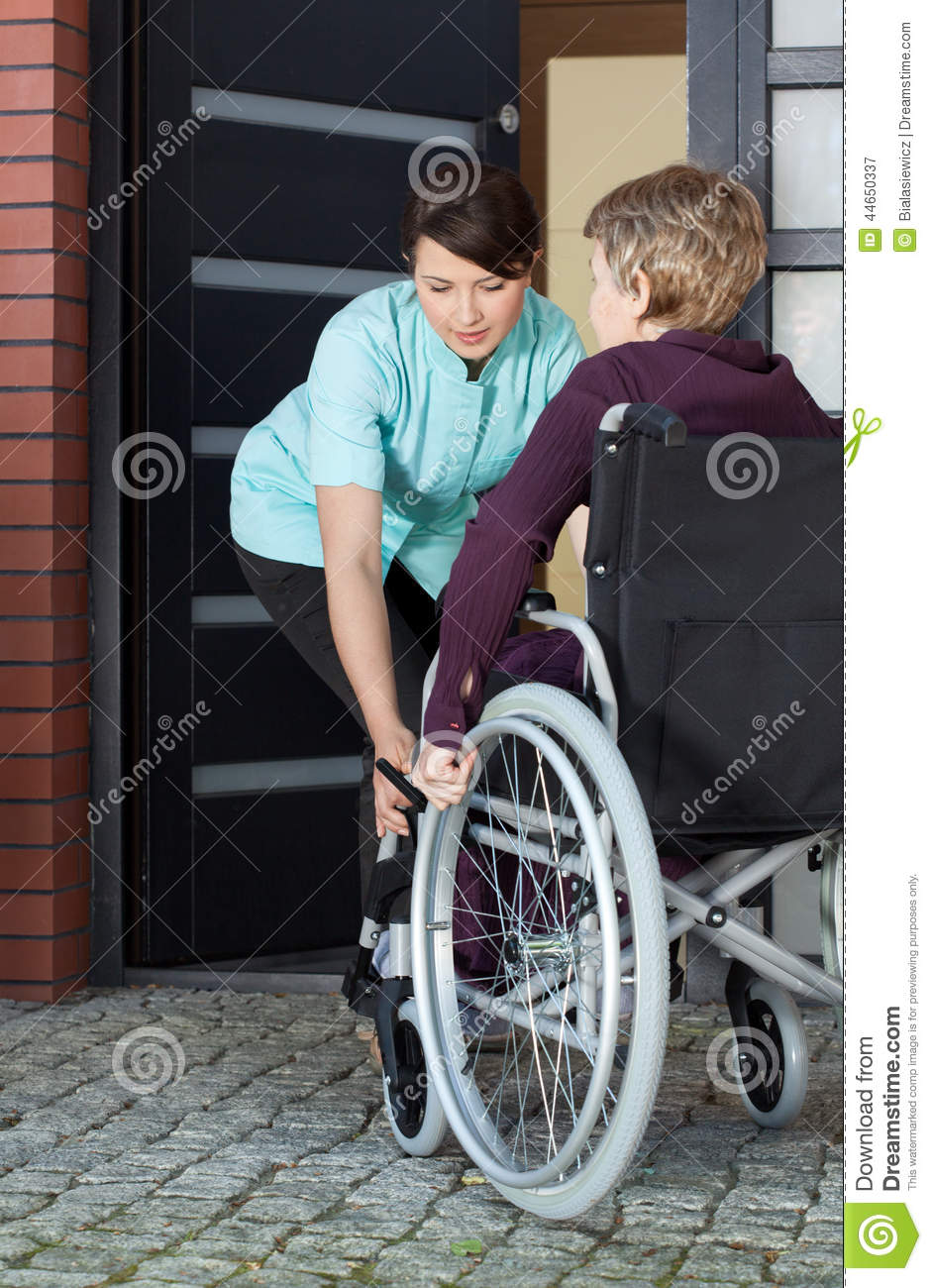Caregiver helping disabled woman entering home stock image for Handicapped wheelchair