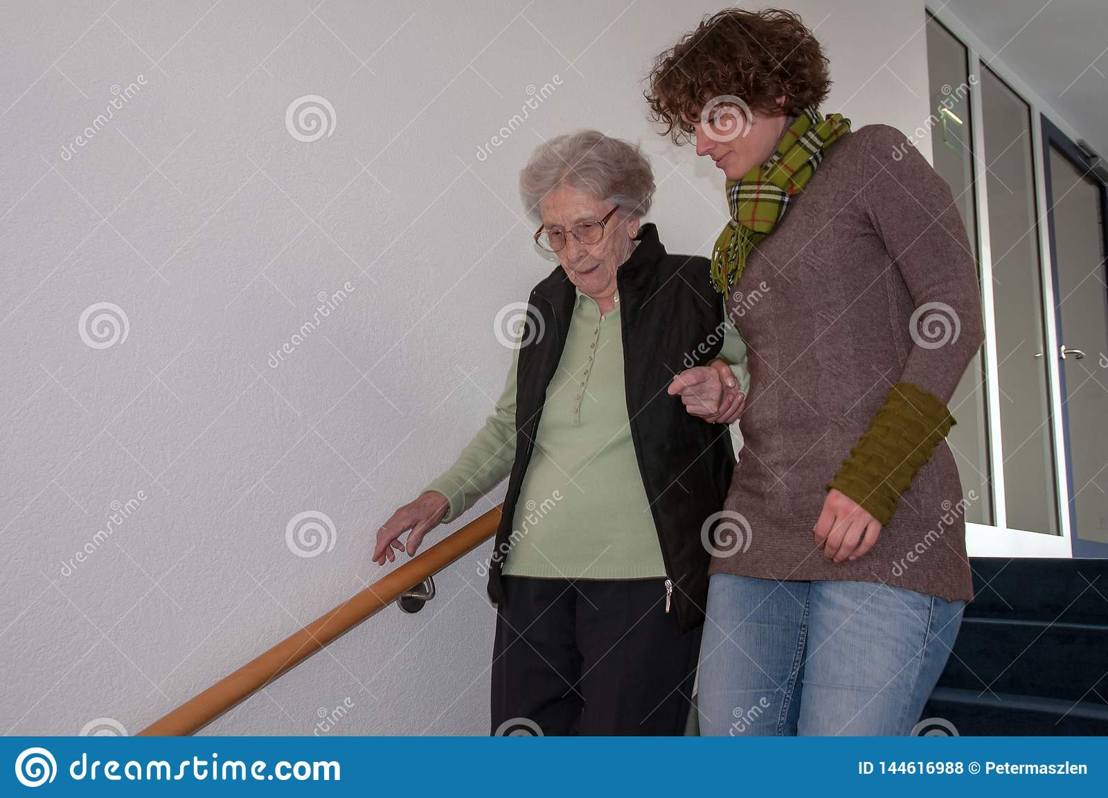 Senior woman going down stairs with helping hands of young woman