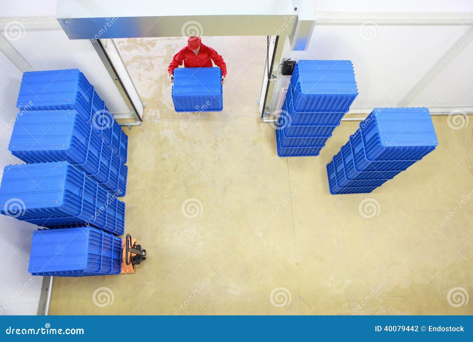 Cargaison - le travailleur dans le bleu uniforme rouge de chargement contiennent