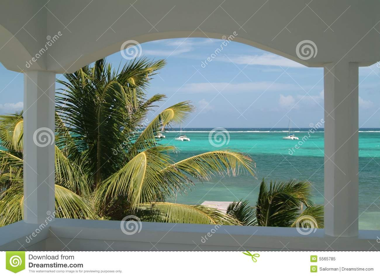 Caribbean Beach Scene With Palm Trees As Seen From A Hotel Balcony