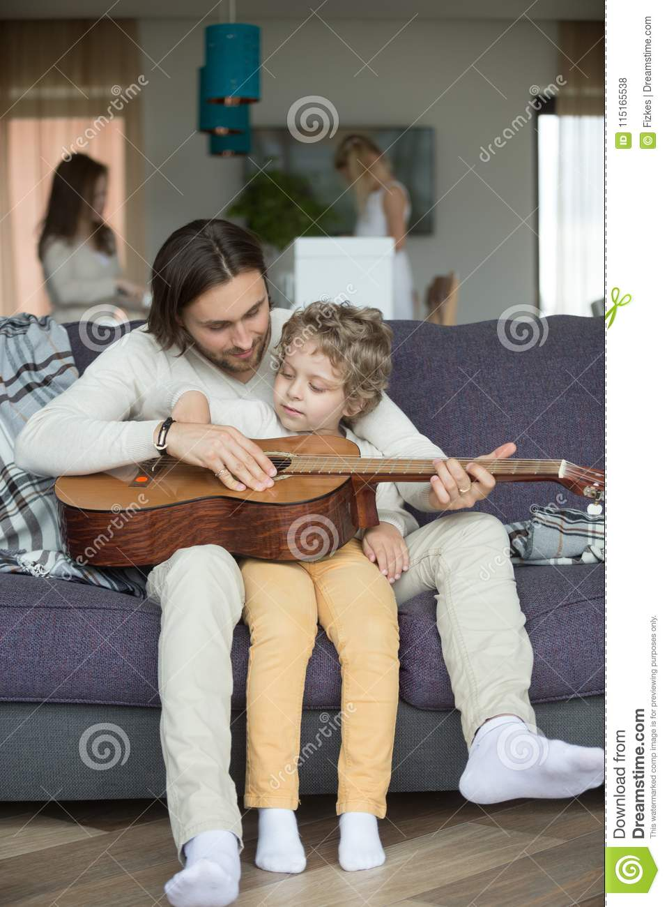 Caring dad teaching kid son to play guitar at home