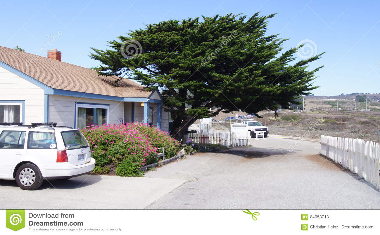 CARMEL, CALIFÓRNIA, ESTADOS UNIDOS - 6 DE OUTUBRO DE 2014: Cypress bonito, uma casa branca e carro ao longo da Costa do Pacífico