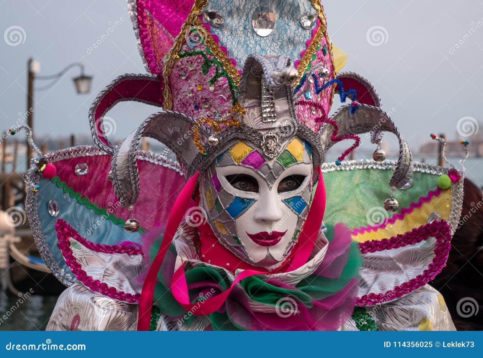 Carnaval-asistente en el traje tradicional que se coloca con de nuevo a Grand Canal, con las góndolas en fondo, durante el carnav
