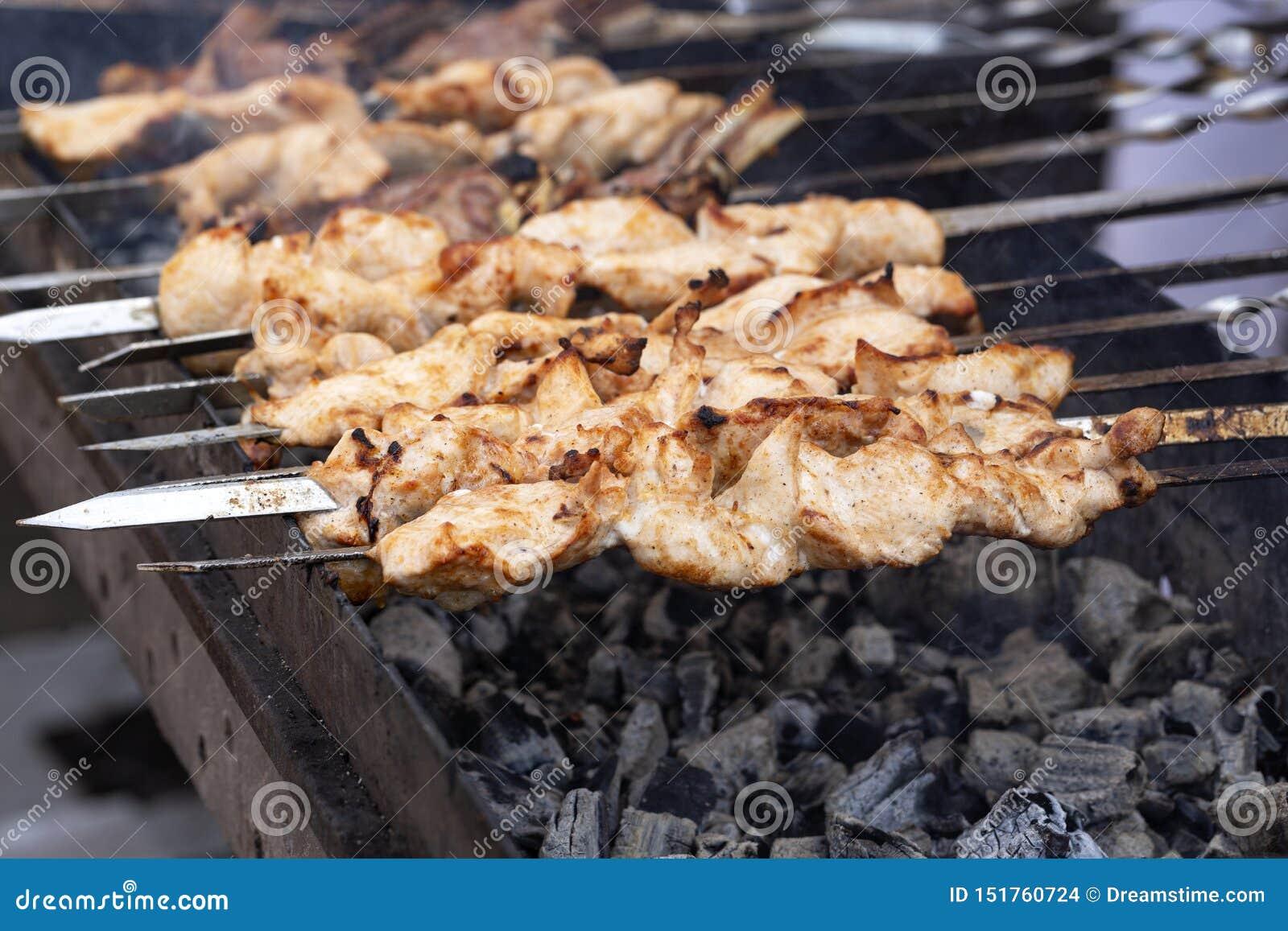 A carne é espetos grelhados em uma grade do assado Churrasco delicioso do no espeto do BBQ na grade aberta, cozinha exterior Alim