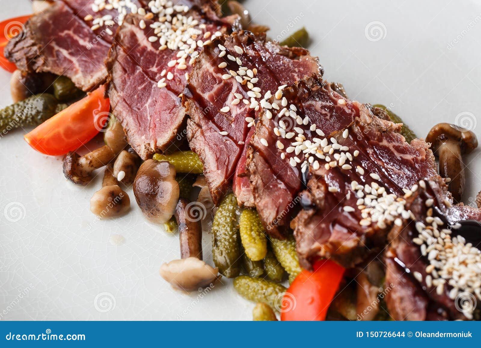 Carne assada rara média cortada com salmouras, tomates de cereja, cogumelos em uma placa branca no fundo de madeira