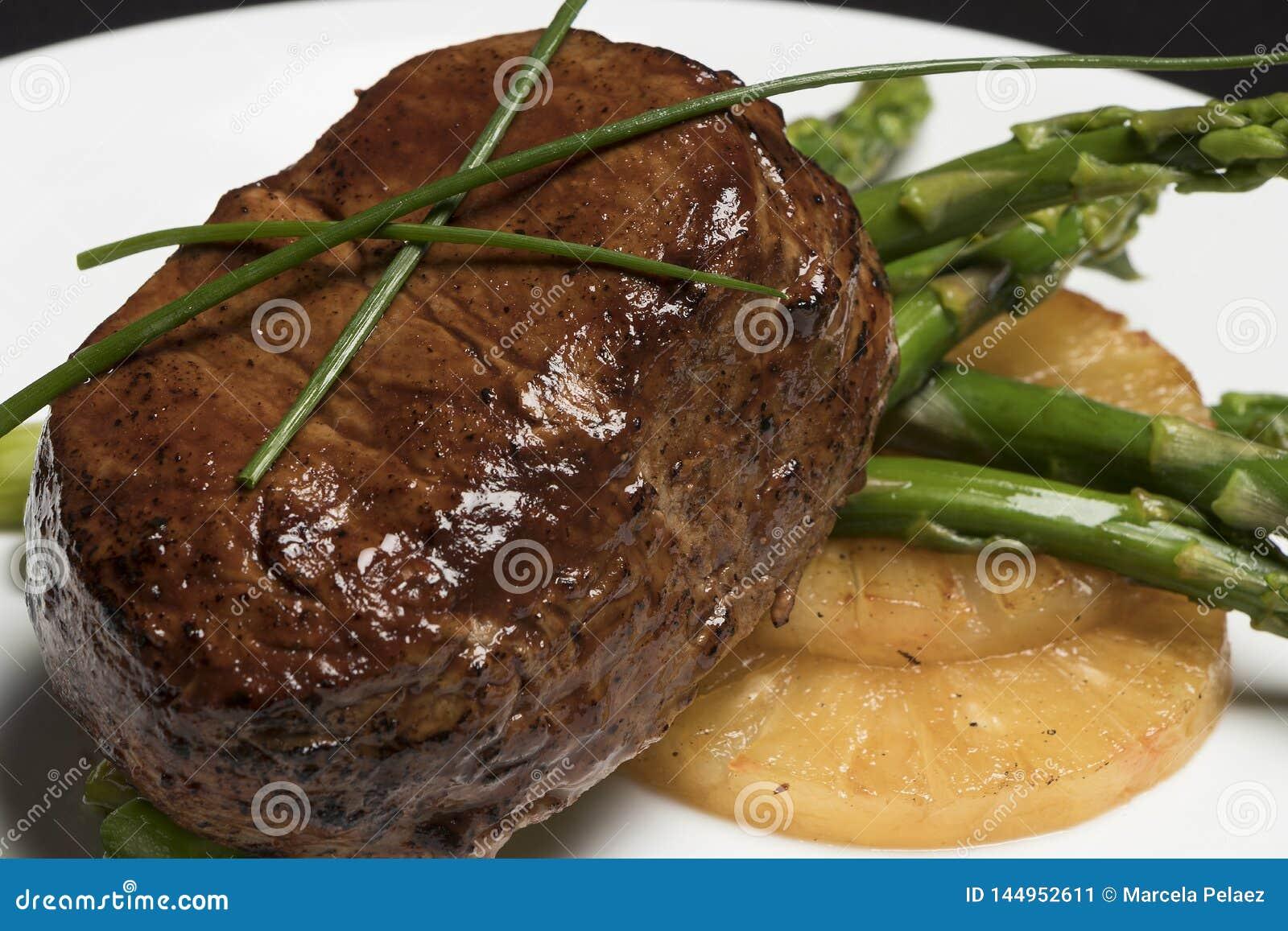 Carne con el espárrago y la piña en la placa blanca y el fondo negro