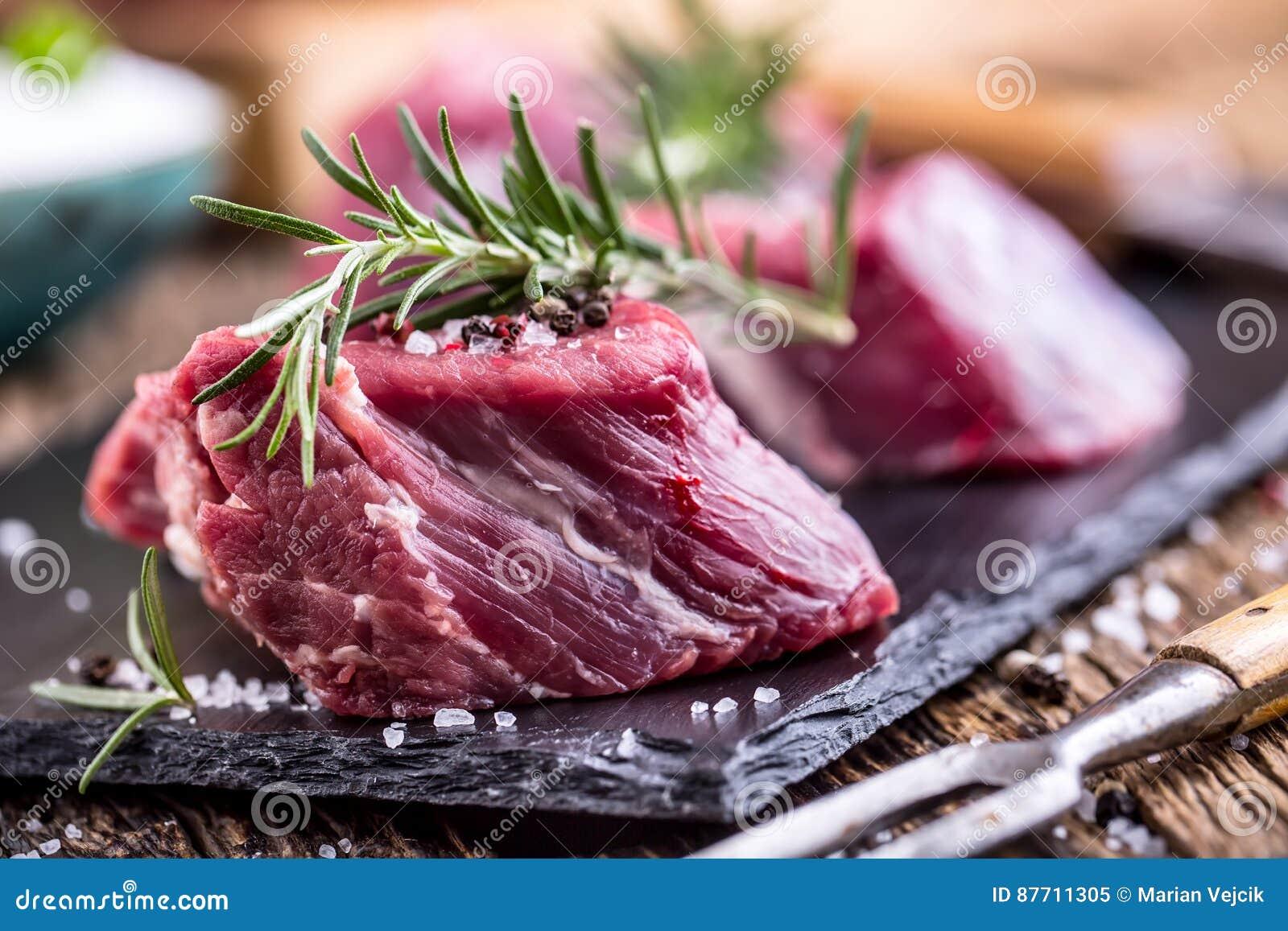 Carne crua da carne O bife cru do lombinho de carne em uma placa de corte com alecrins salpica o sal em outras posições