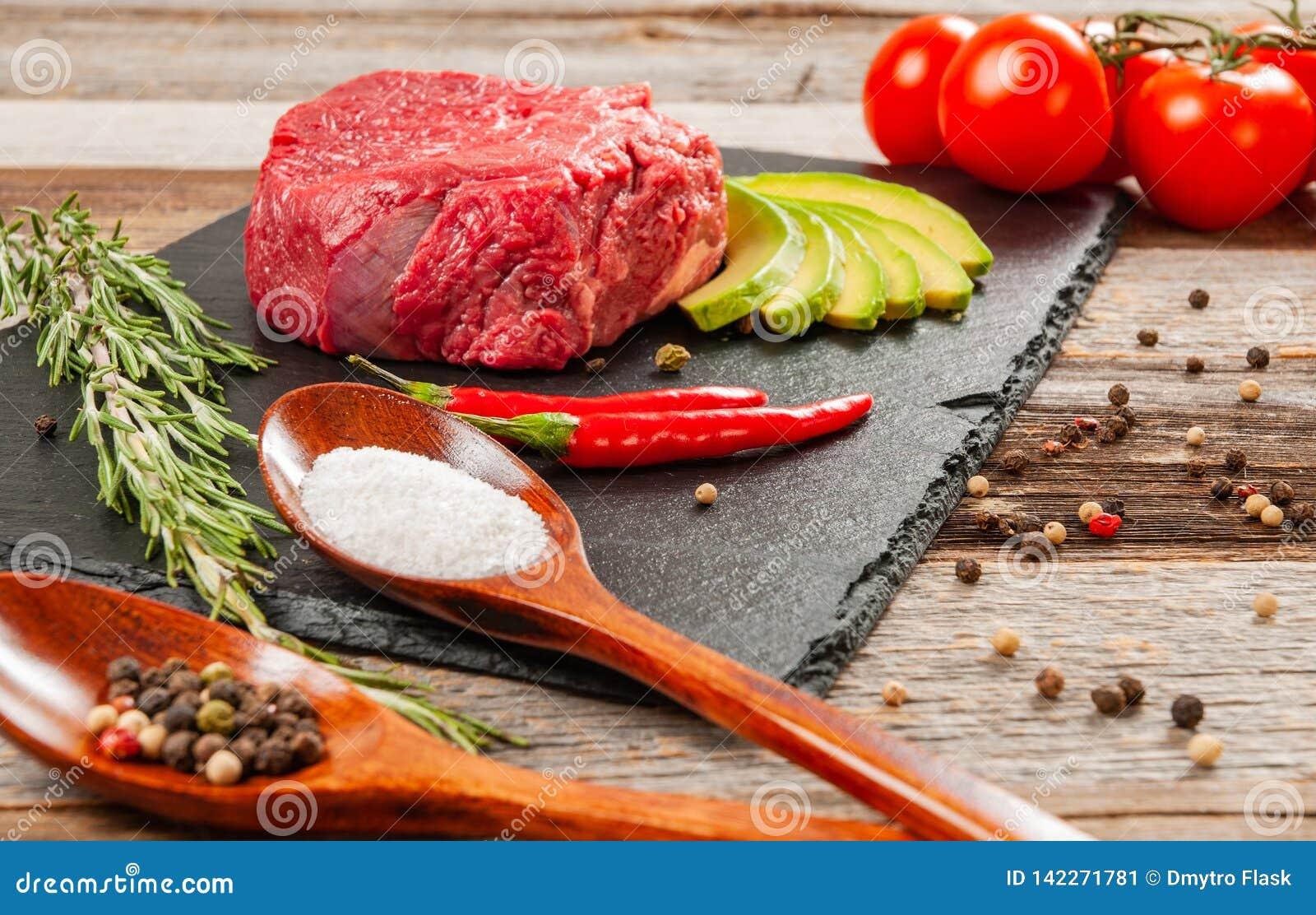 Carne cruda, carne de vaca con las especias para cocinar en tablero negro