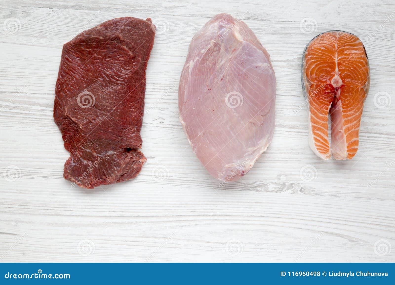 Carne cruda cruda del manzo, seno di tacchino e bistecca di color salmone su fondo di legno bianco, vista superiore Disposizione