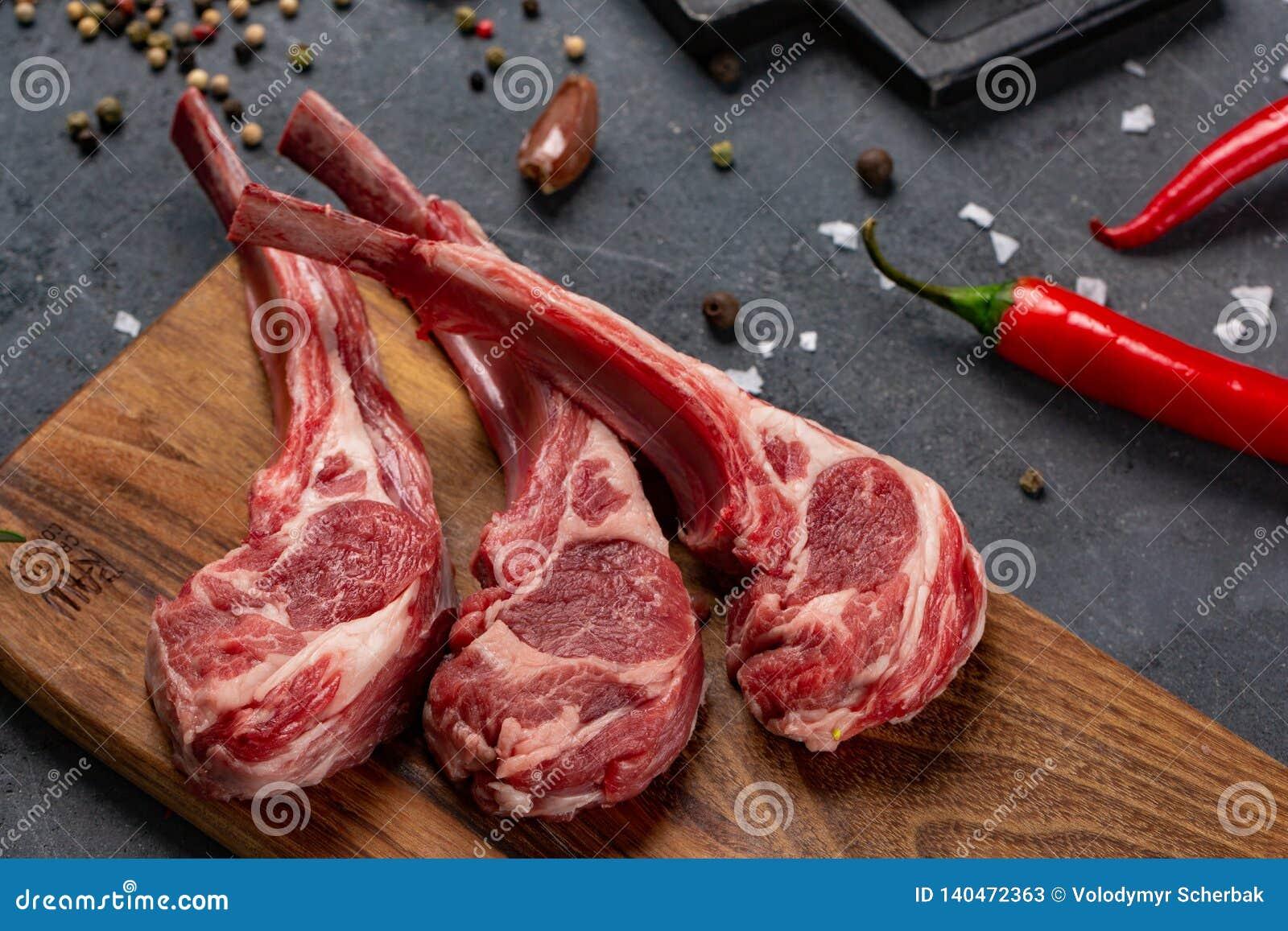 Carne cruda en el hueso con los chiles y las especias, fondo negro para cocinar con el espacio de la copia, visión superior