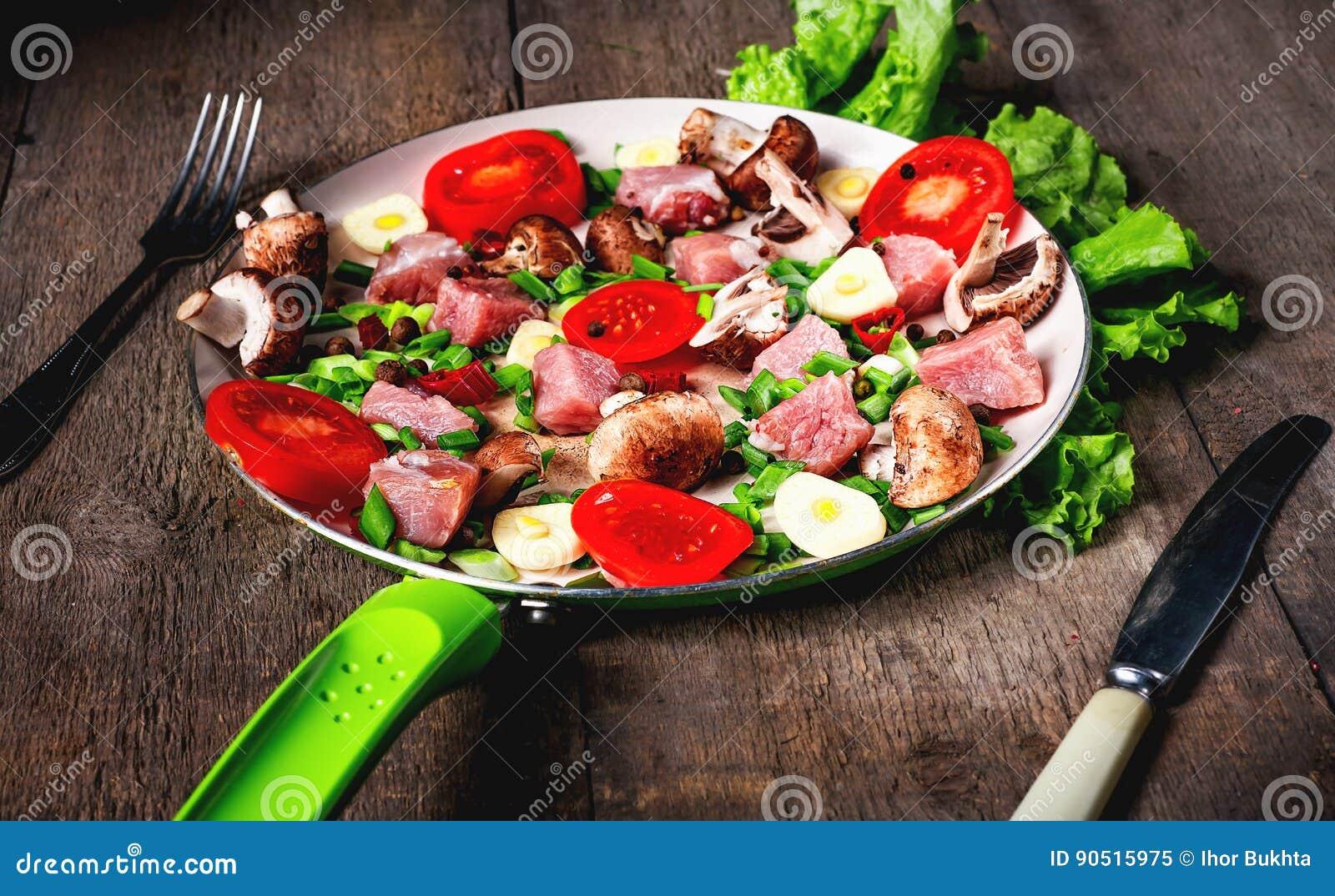 Carne cruda in piatto e padella, spezie, coltello sulla tavola di legno,