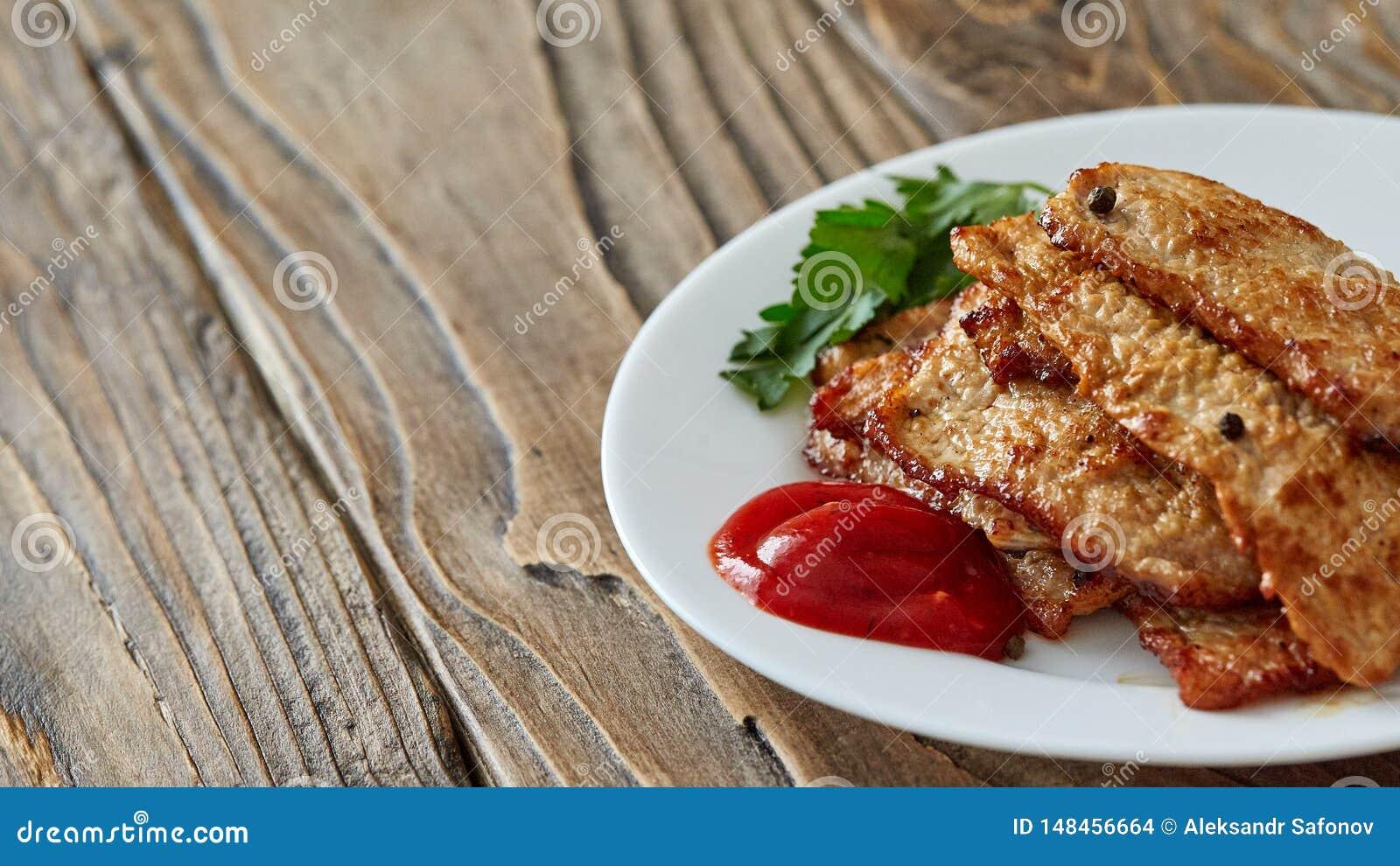 Carne de la carne asada en una placa en una tabla de madera