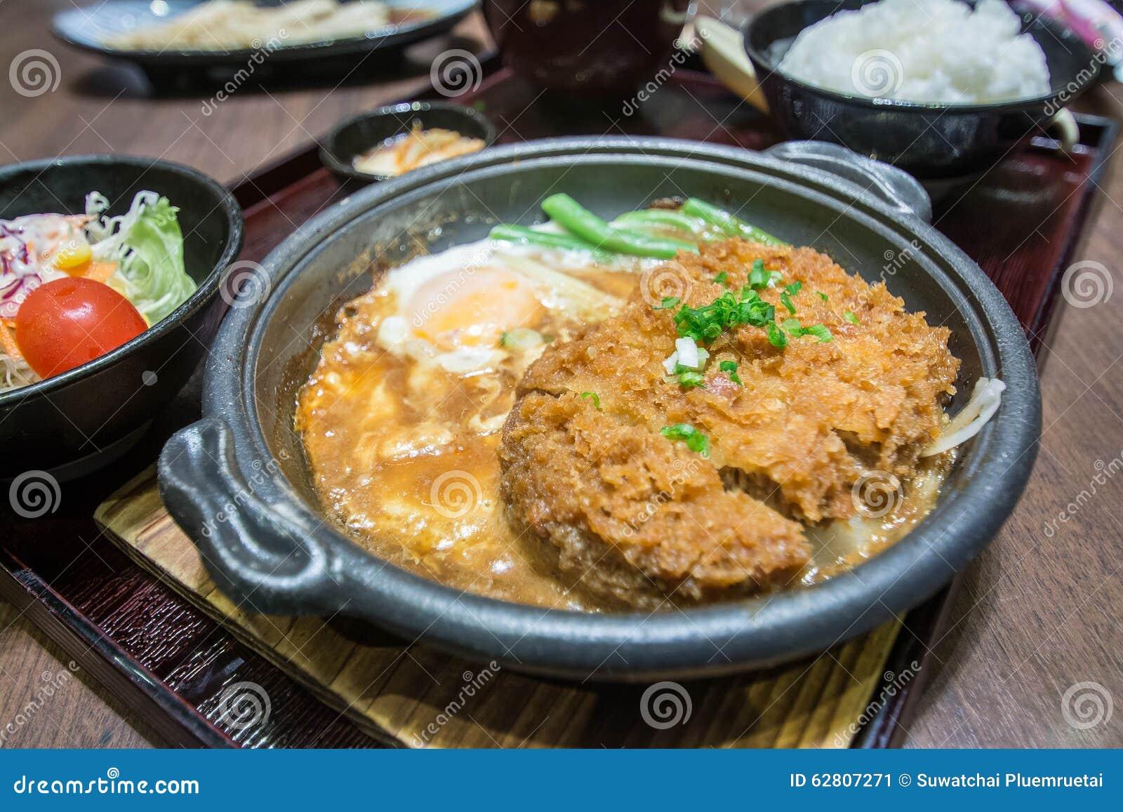 Carne de porco ateada fogo profunda fervida com parte superior fresca do ovo na bacia de arroz