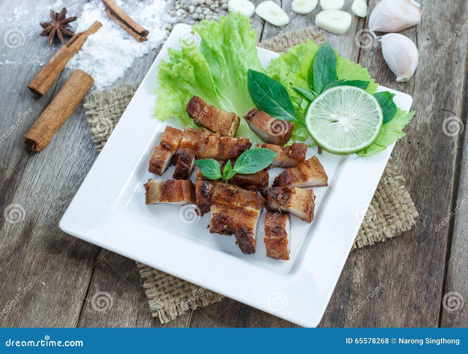 Carne de porco friável com alho e pimenta na placa branca