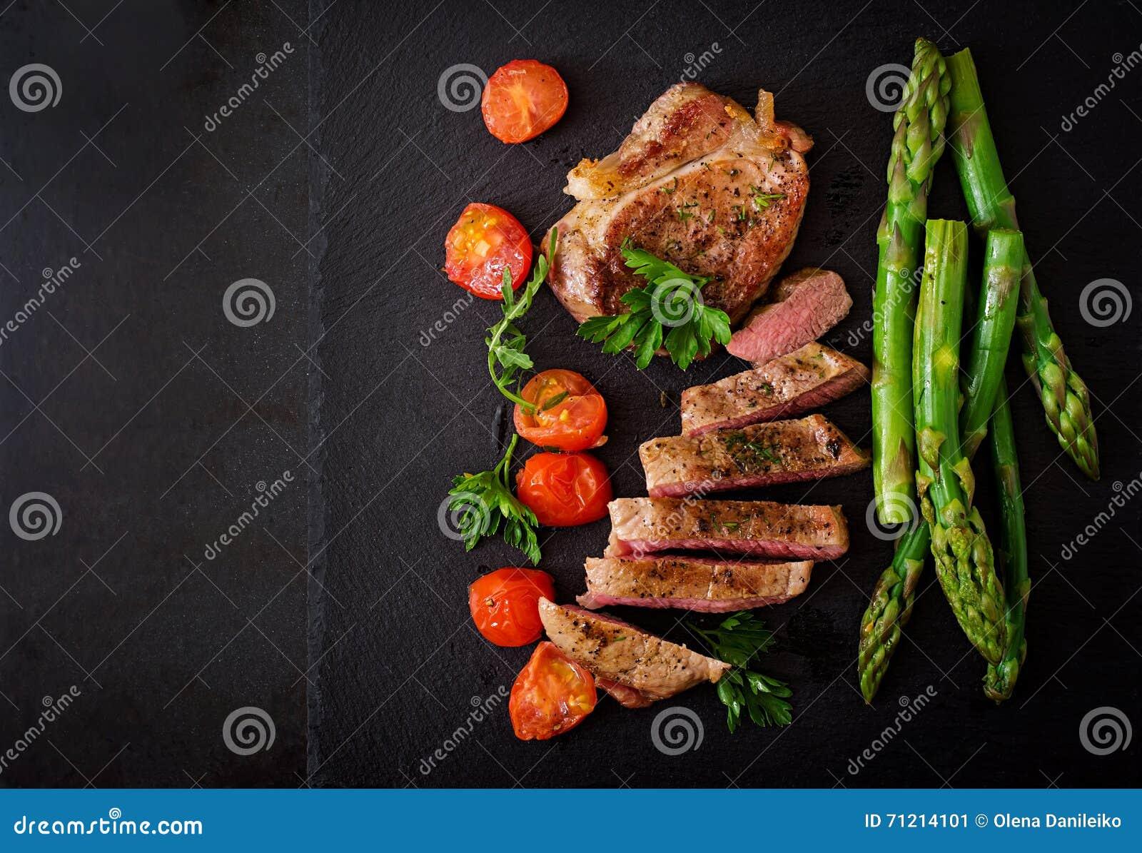 Carne de vaca jugosa del hecho del filete con las especias y los tomates, espárrago