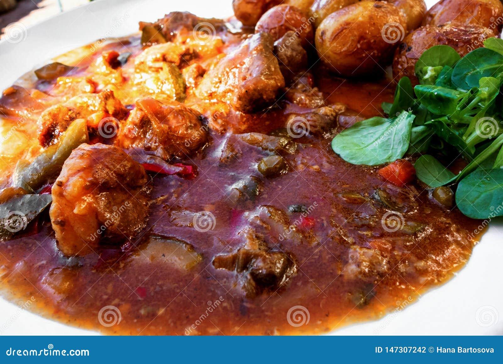 Carne dell agnello in salsa, patata e foglia di verdure selvagge