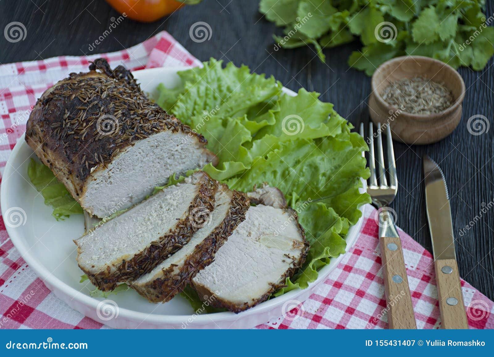 Carne di maiale bollita Baked in spezie affettate su un piatto bianco con insalata verde Priorit? bassa di legno scura