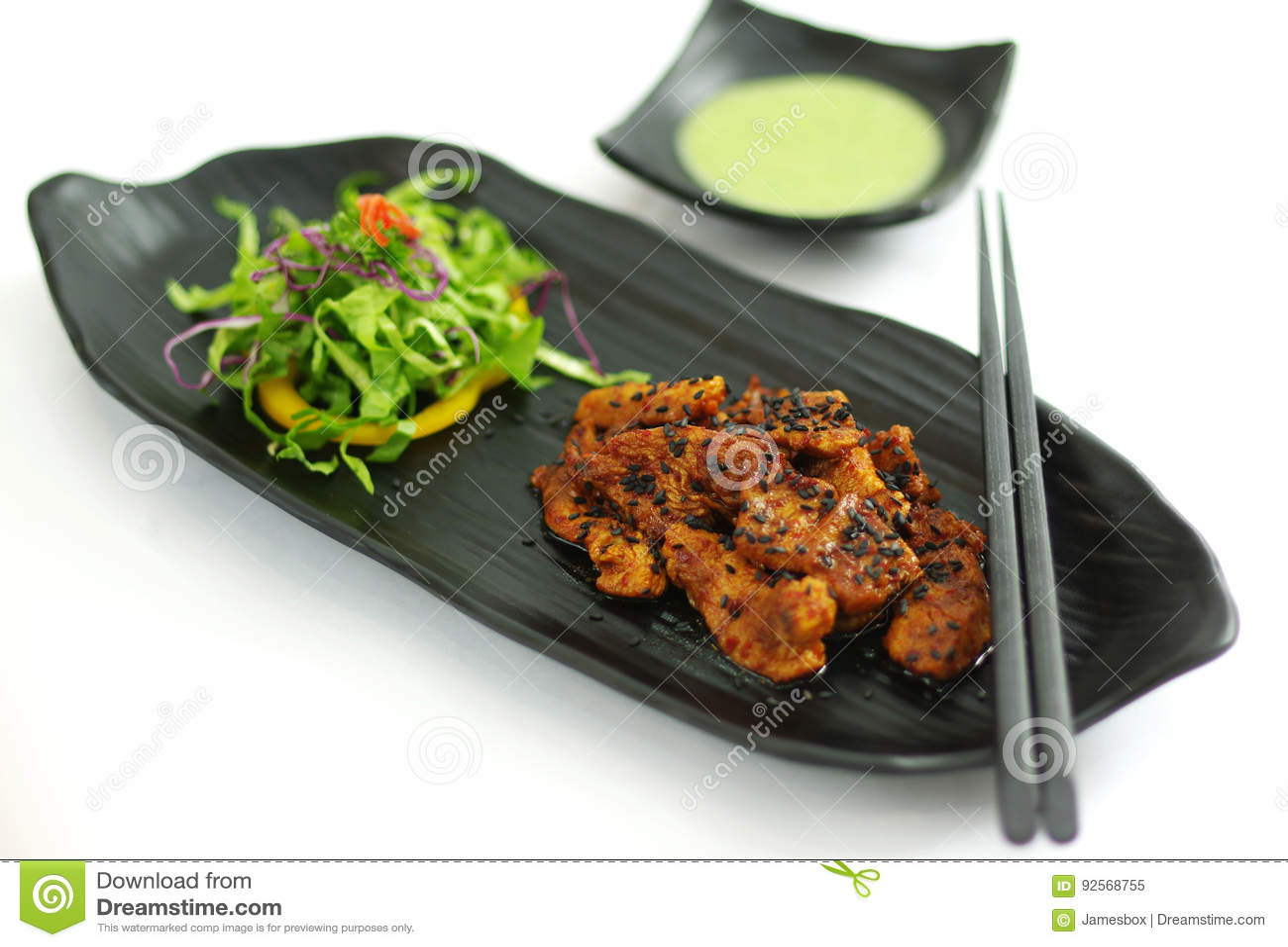 Carne di maiale brasata con la salsa di peperoncino rosso, il seasame e l insalata su platte nera