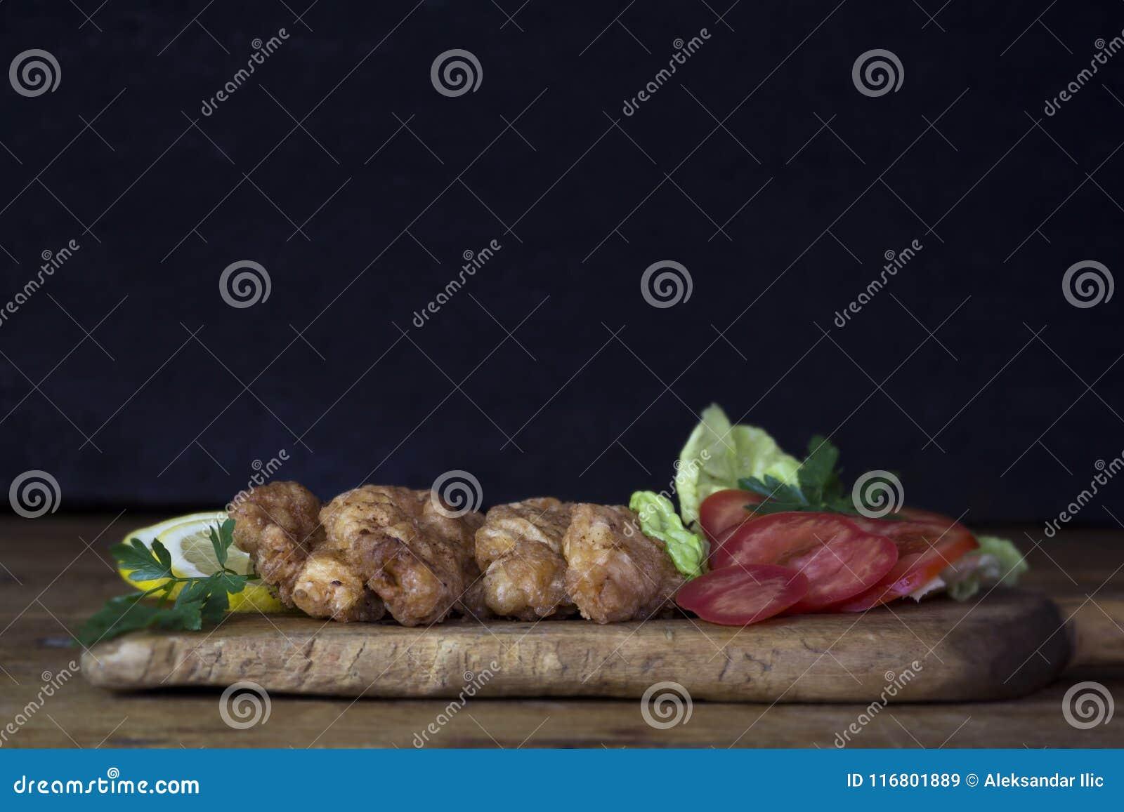 Carne di pollo impanata con insalata ed il limone che riposano su un Wo rustico