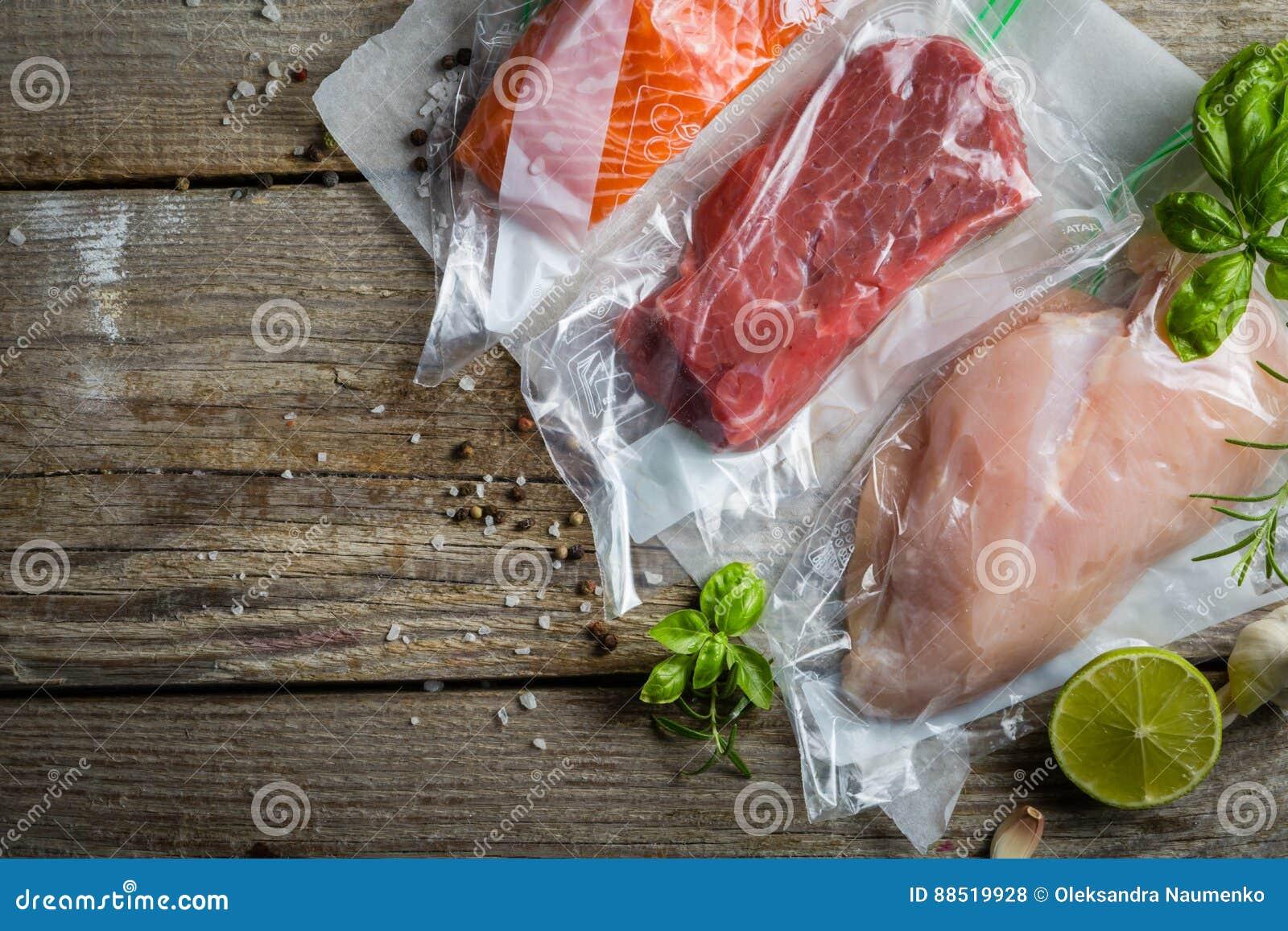 Carne, galinha e salmões no saco de plástico do vácuo para o cozimento sous do vide