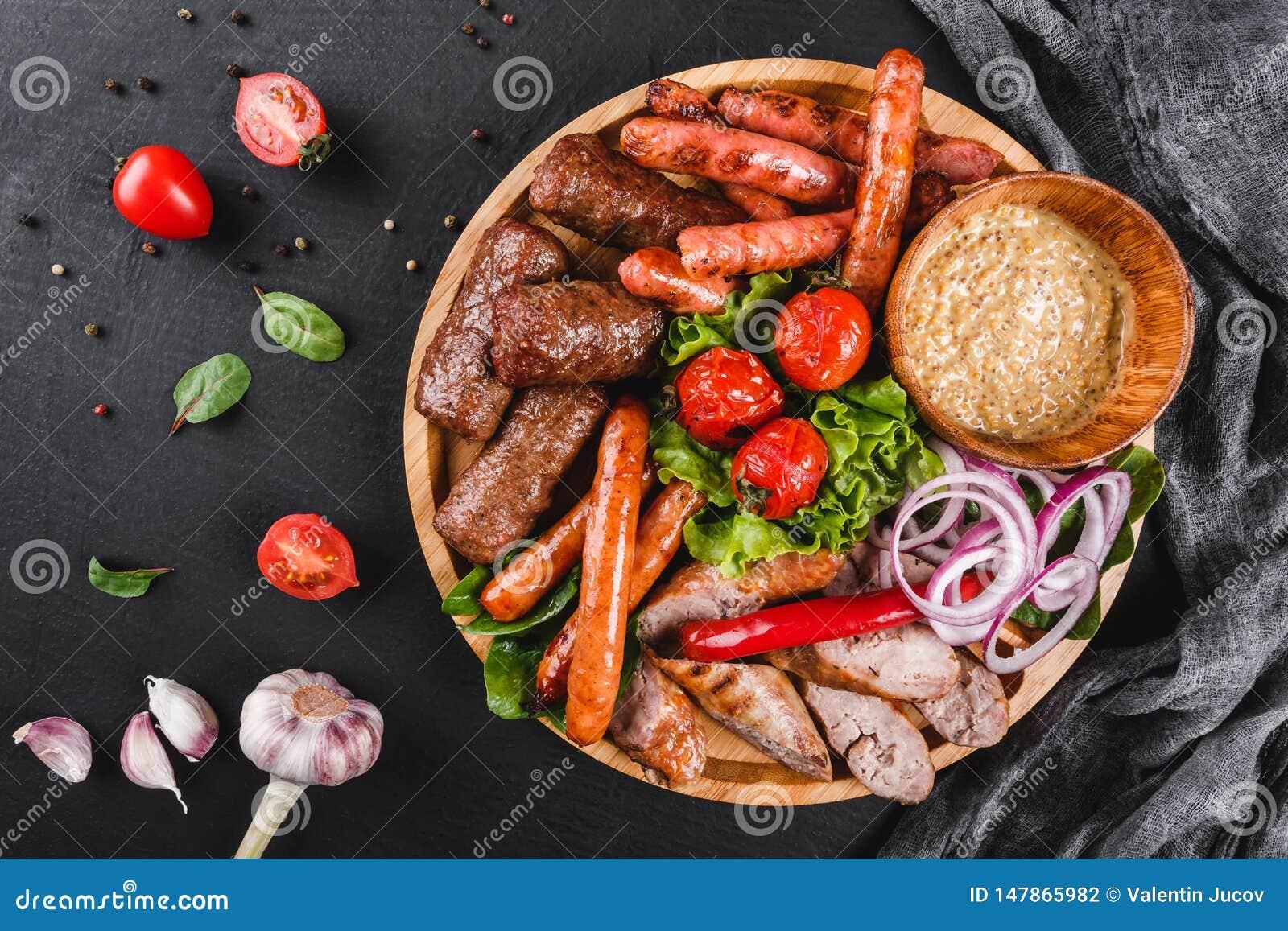 Carne grelhada deliciosa sortido e salsichas com tomates e molho do BBQ na placa de corte sobre o fundo de pedra preto Carne quen