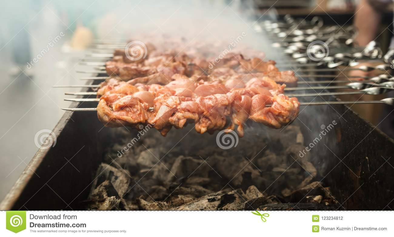 Carne grelhada do assado em espetos sobre o fogo com o fumo que cozinha em um carvão