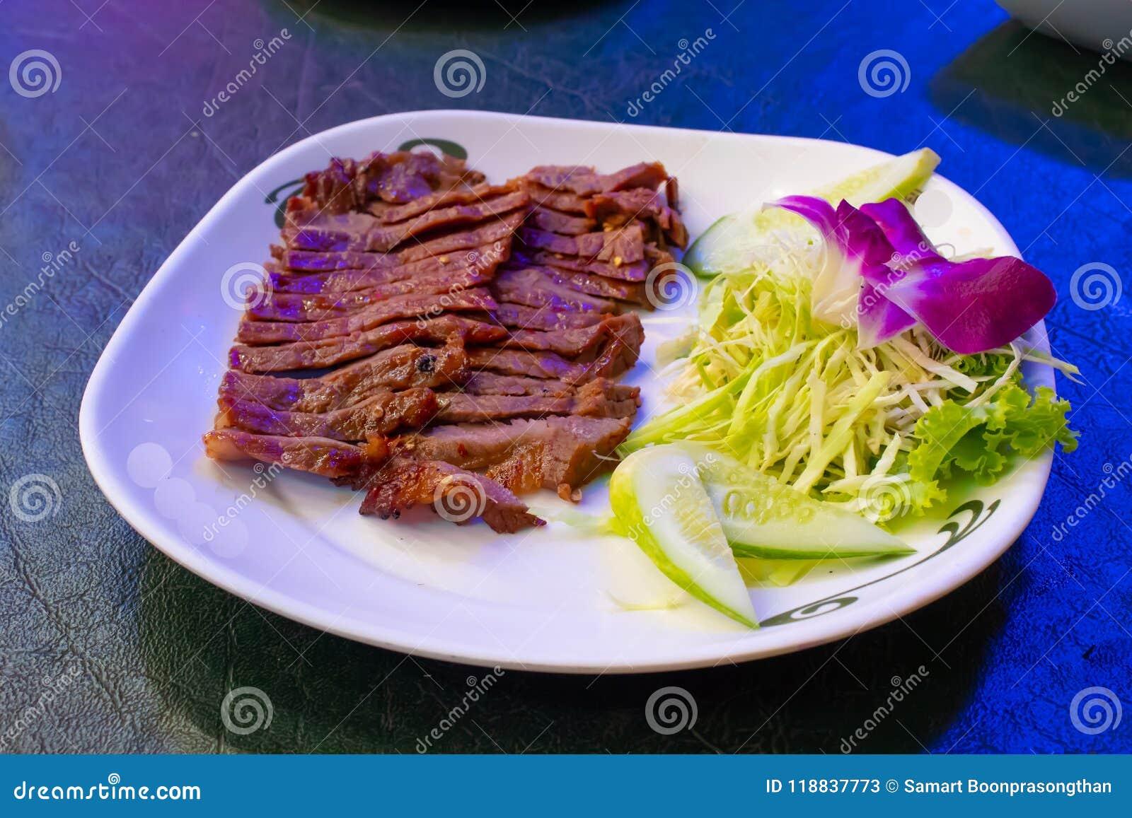 Carne grelhada em uma placa branca com o molho e os vegetais