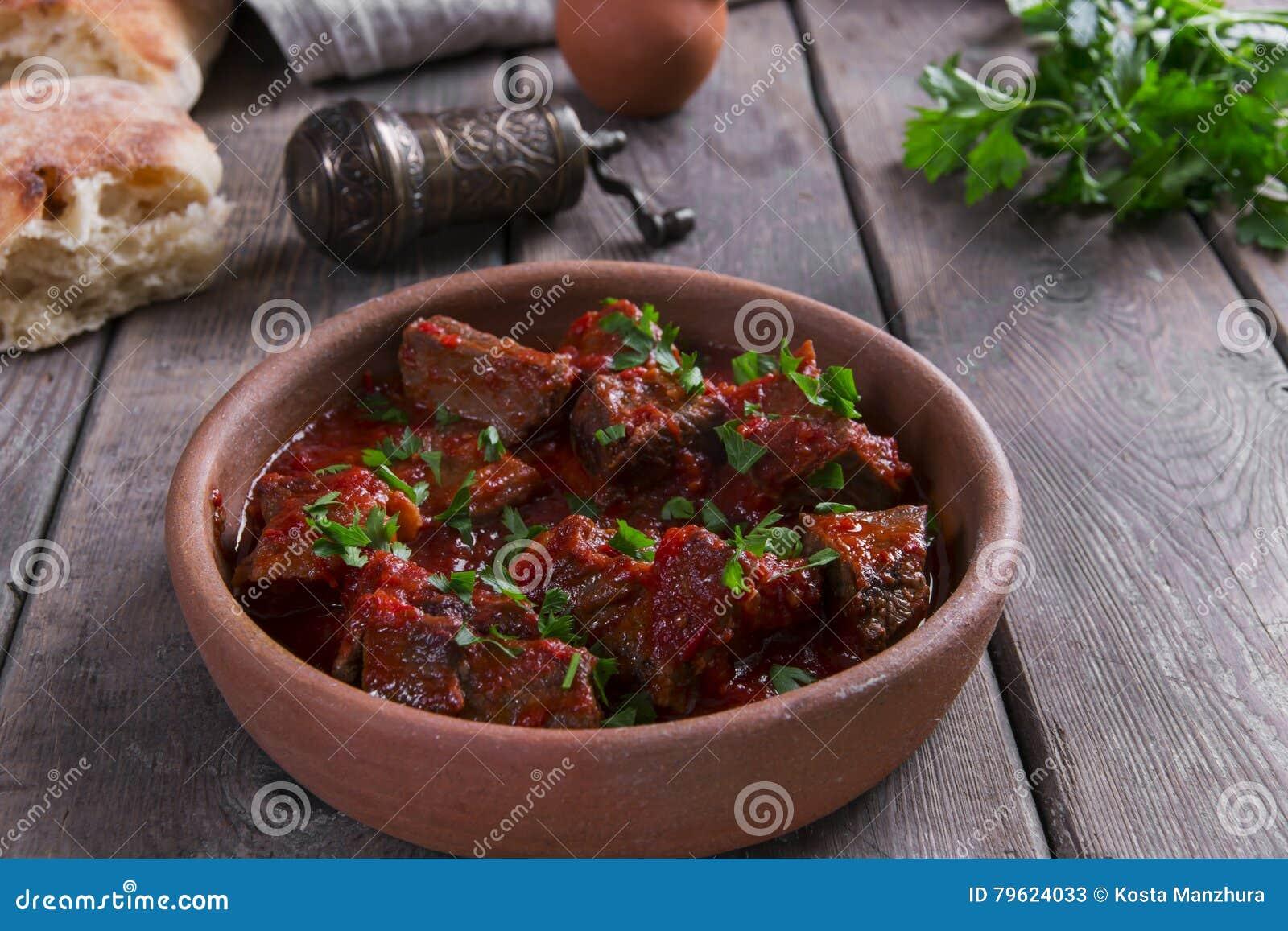 Carne no assado de carne do molho de tomate em uma bacia da argila