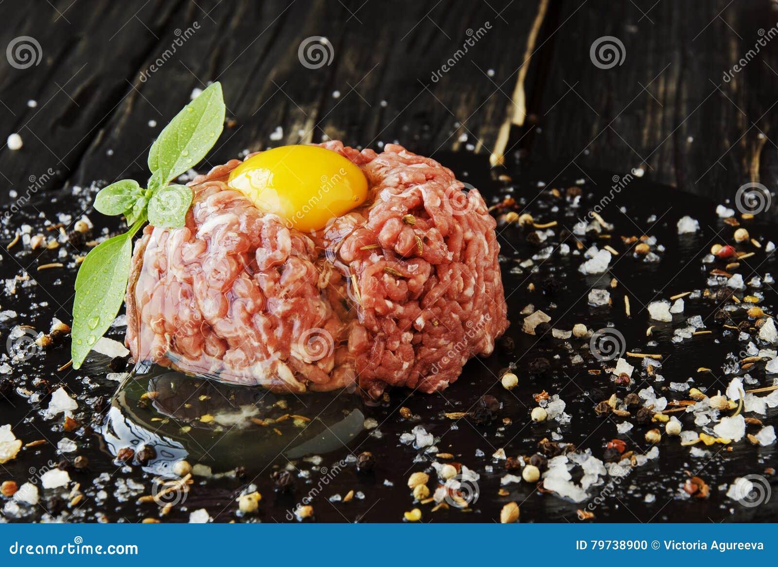 Carne picadita cruda, verduras con la sal y especias, foco selectivo