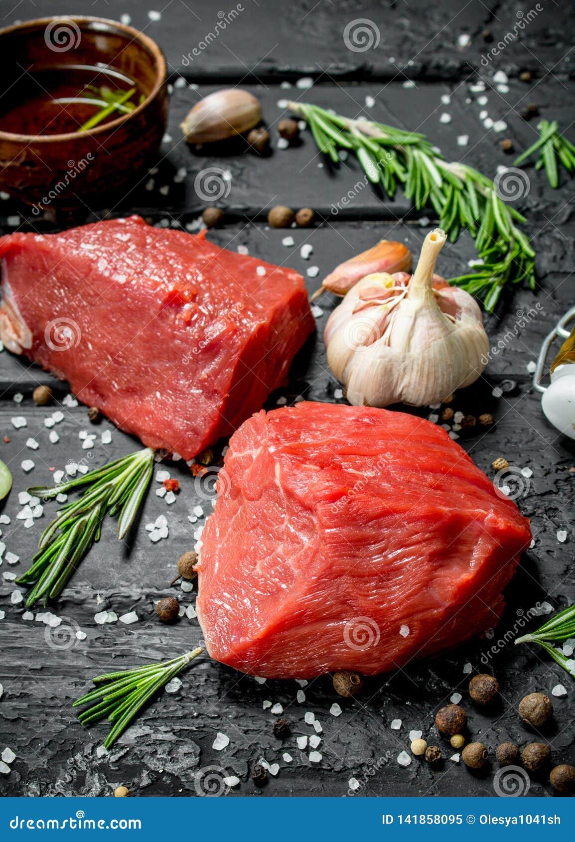 Carne sin procesar Pedazos cortados de carne de vaca con las especias y las hierbas en un tablero de madera