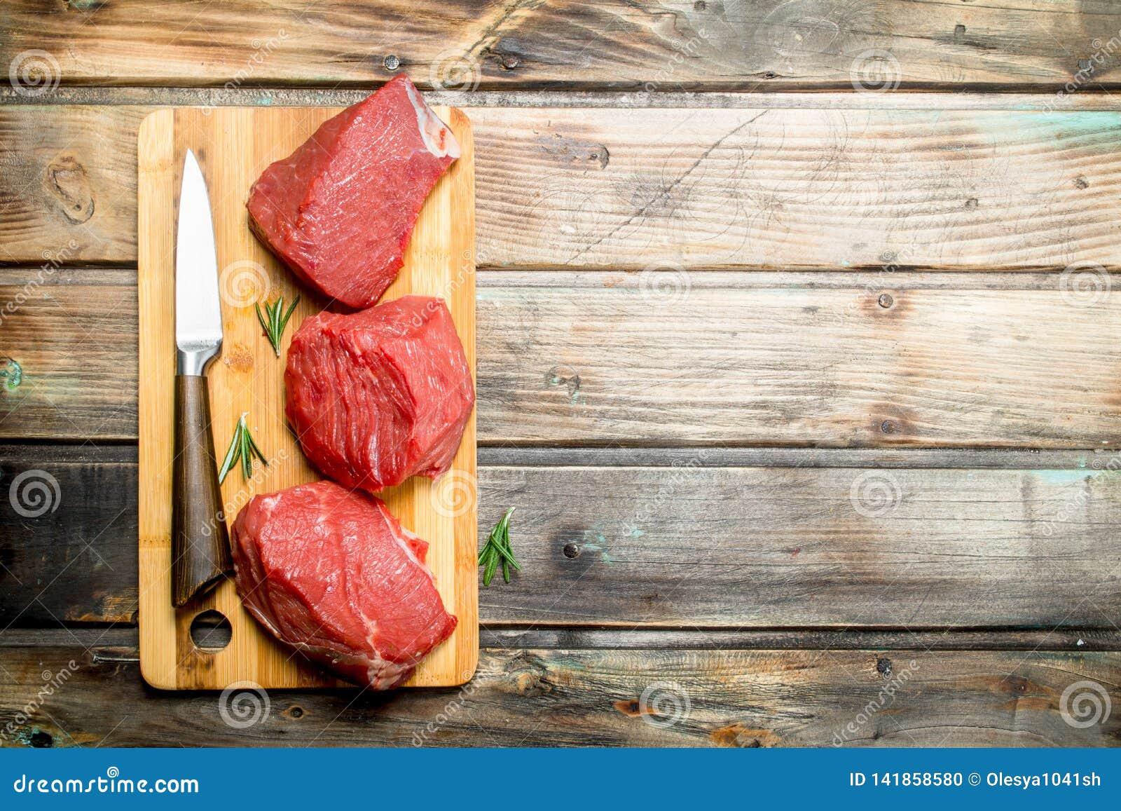 Carne sin procesar Pedazos de carne de vaca con un cuchillo