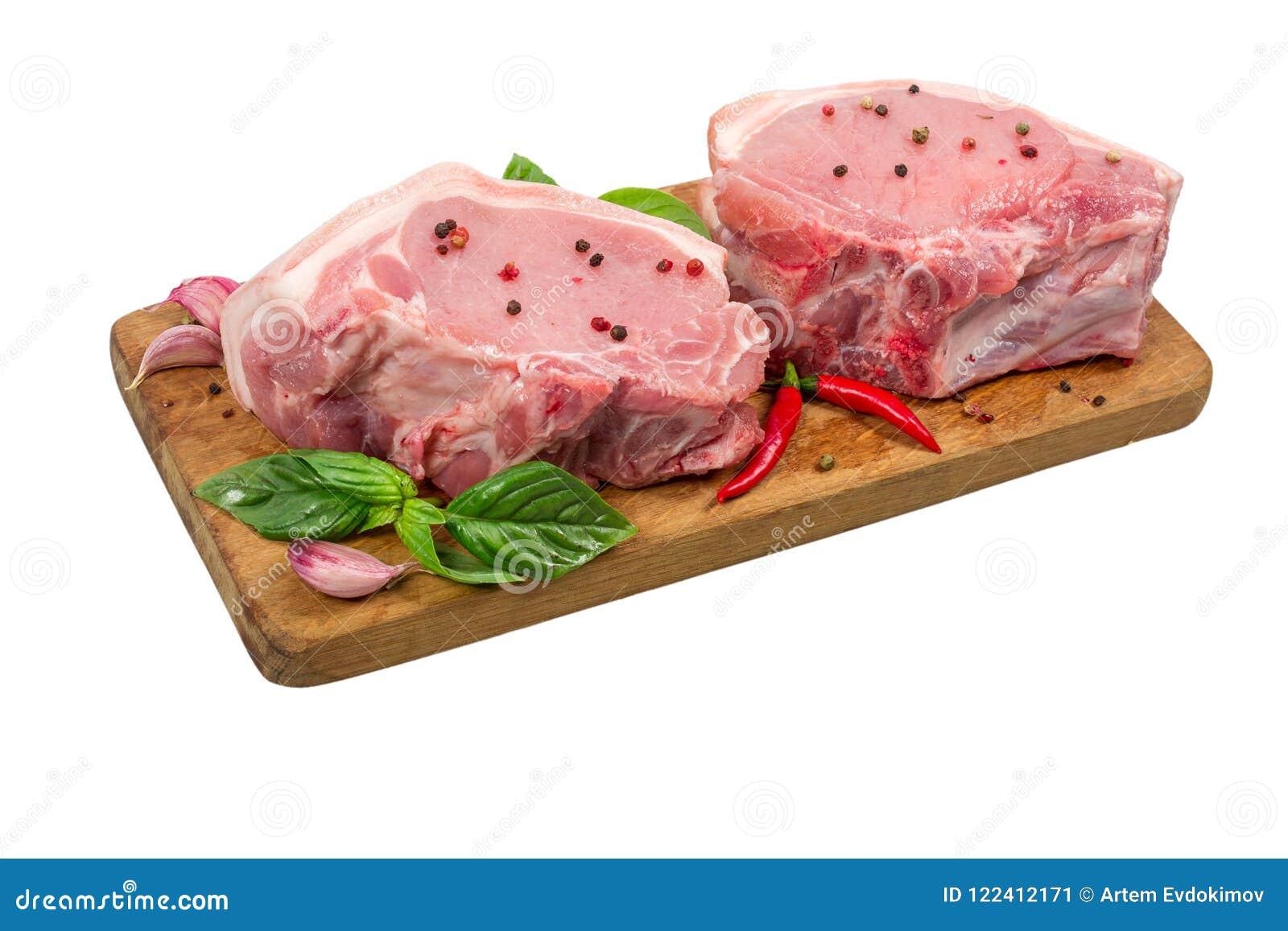 Carne suina cruda sul tagliere di legno con le erbe e le spezie isolate su fondo bianco Cottura del concetto