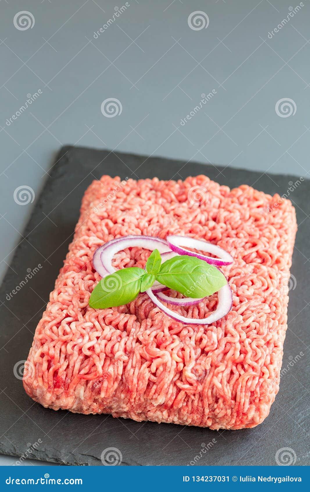 Carne tritata da carne di maiale e da manzo, carne macinata sul bordo scuro dell ardesia, verticale, spazio della copia