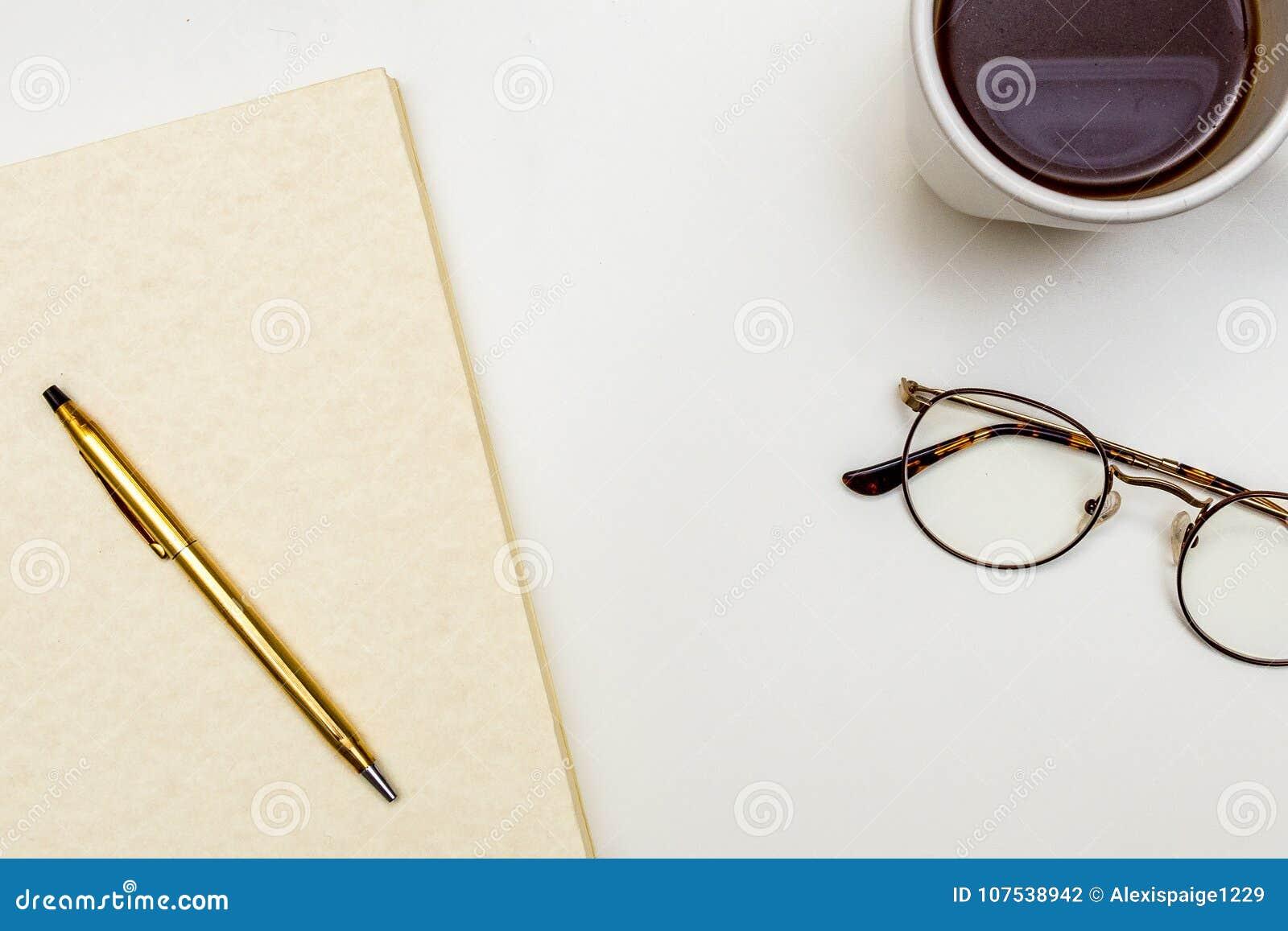 Carnet avec de l or Pen Eye Glasses Coffee sur un Tableau blanc de configuration ci-dessus d appartement