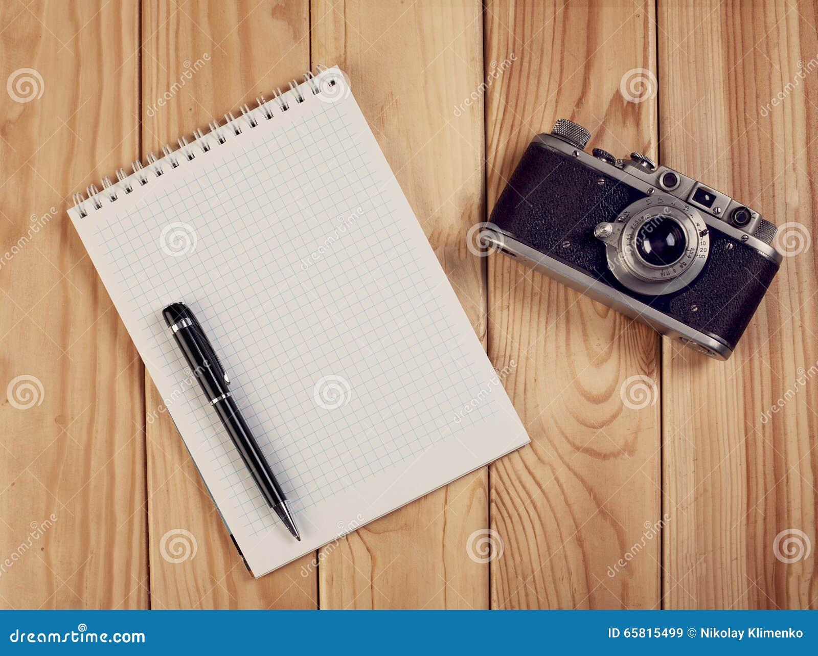 Carnet avec l appareil-photo de stylo et de vintage sur le bureau en bois Vue supérieure
