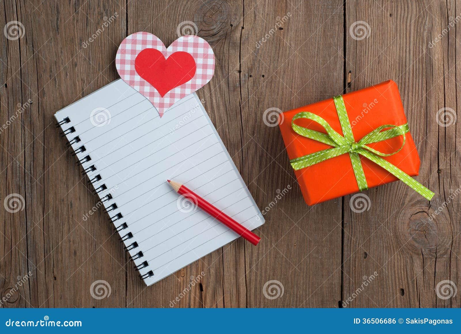 Carnet avec le cadeau, le crayon et les coeurs