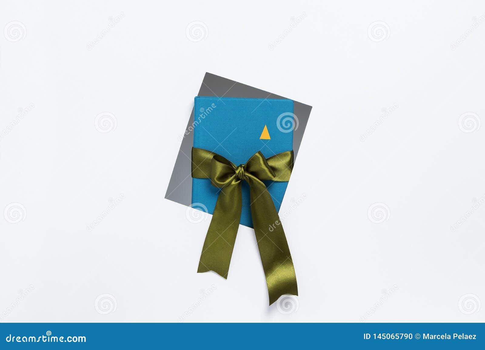 Carnet avec le ruban de cadeau sortant du cadre sur le fond blanc