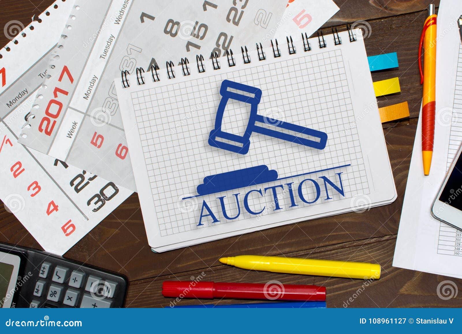 Carnet avec ventes aux enchères en ligne de notes sur la table de bureau avec des outils