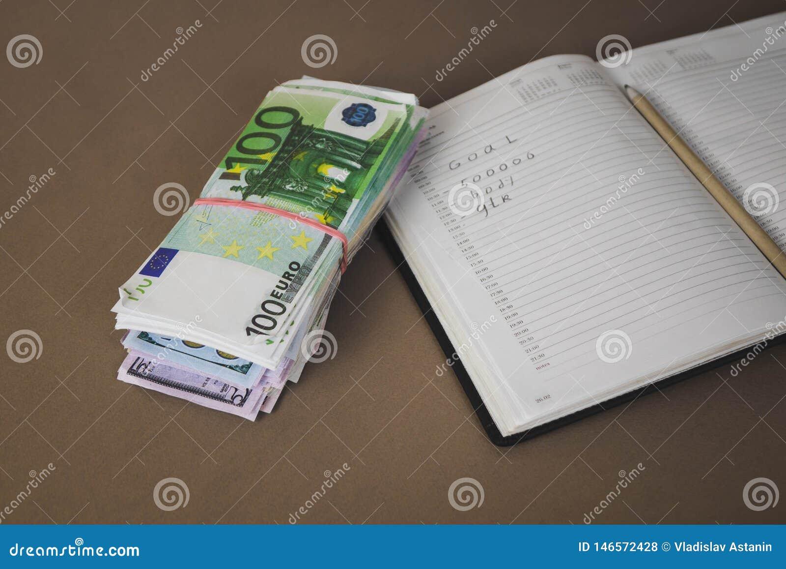 Carnet blanc sur le fond de cent fins d argent liquide d euro