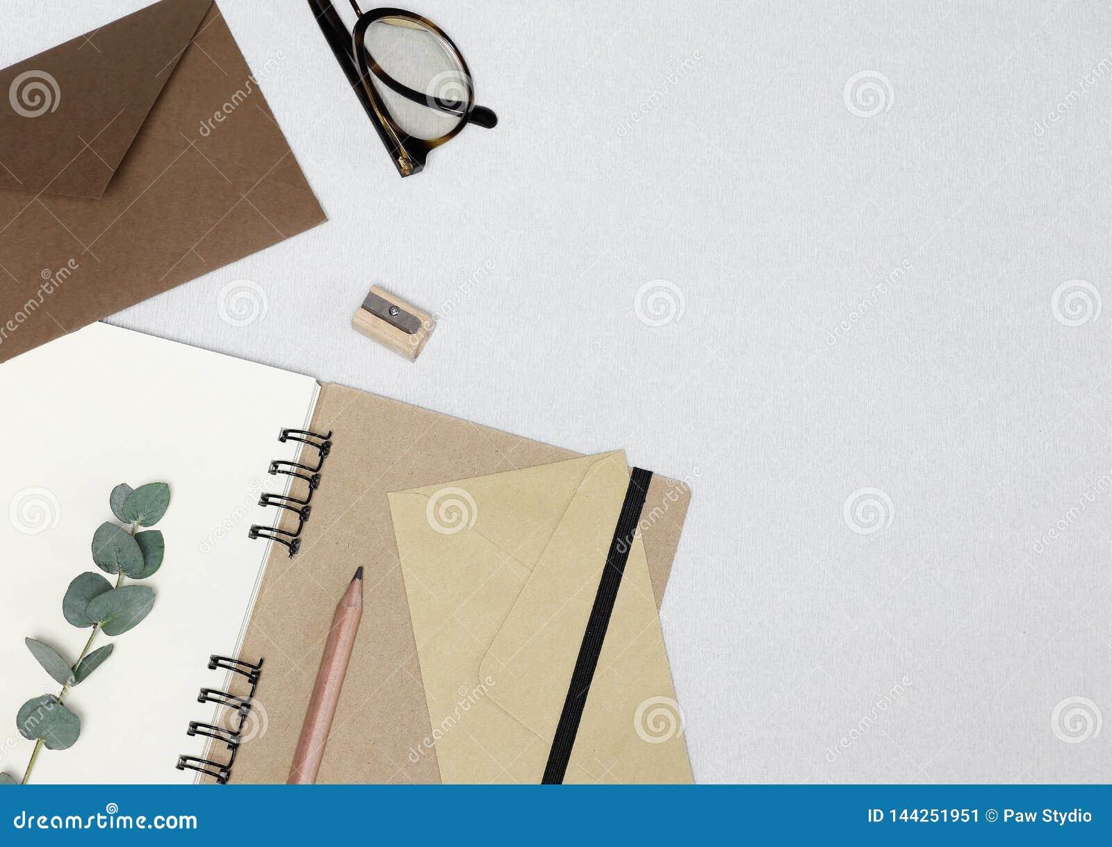 Carnet, crayon, affûteuse, lunettes, enveloppes, branche d eucalyptus sur le fond blanc