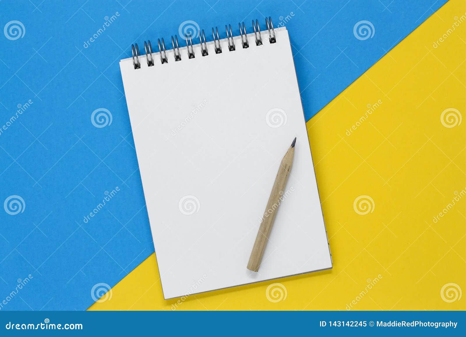 Carnet de notes à spirale ouvert avec une page vide et un crayon sur un fond bleu et jaune, avec l espace de copie