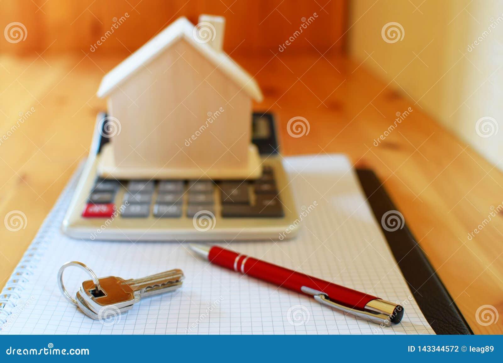 Carnet de papier avec la calculatrice, le modèle de maison, les clés et le stylo sur la table en bois