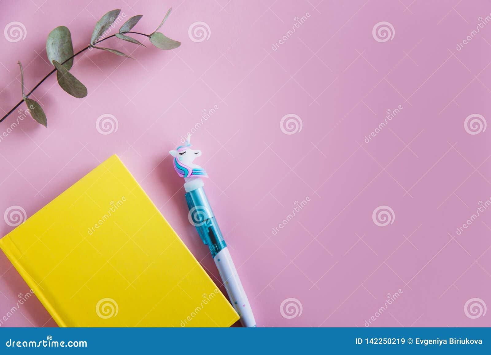 Carnet jaune pour les notes, le stylo drôle de licorne et les feuilles vertes d eucalyptus sur le fond en pastel rose Configurati