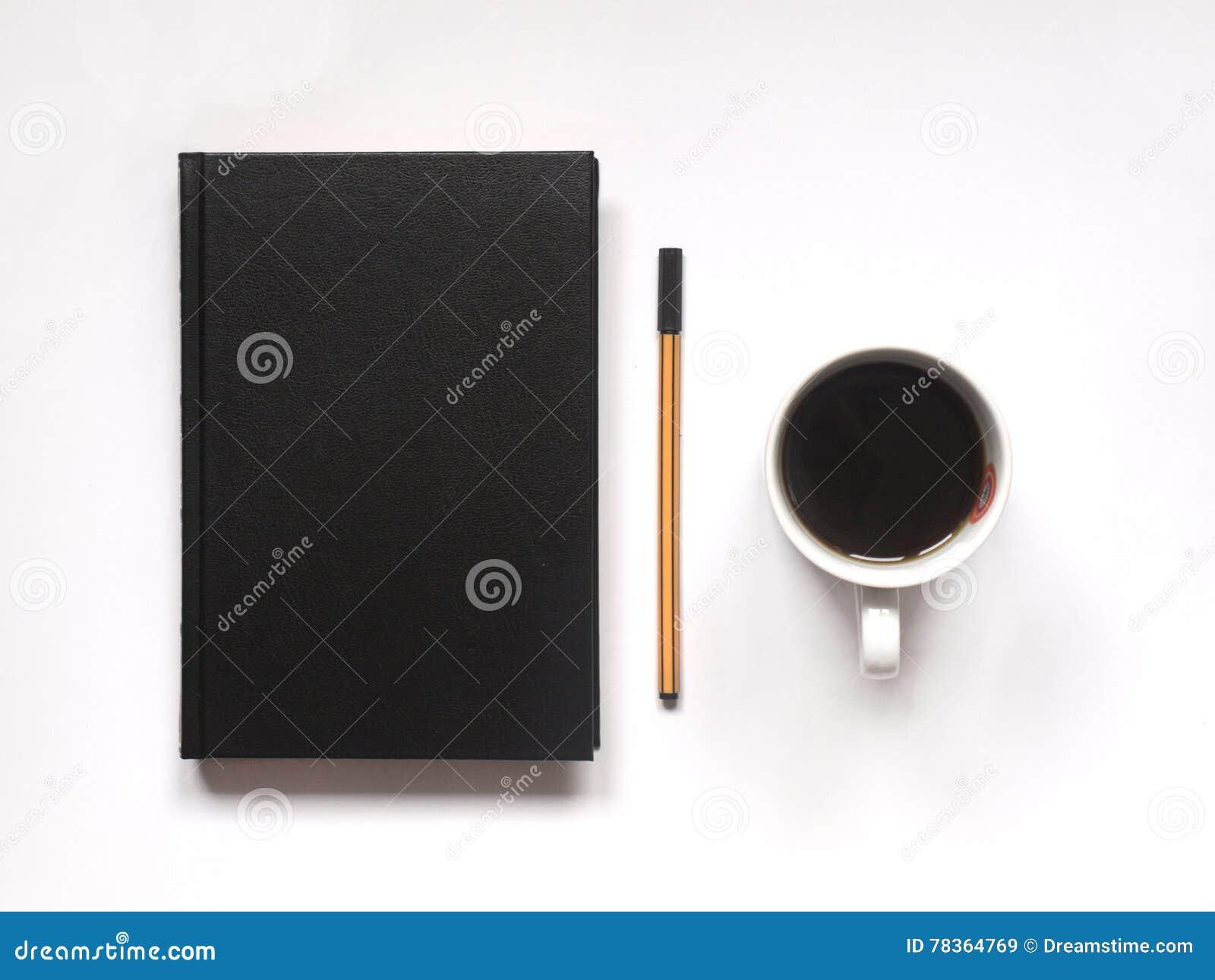 Carnet ou livre avec le stylo et café noir chaud sur le bureau