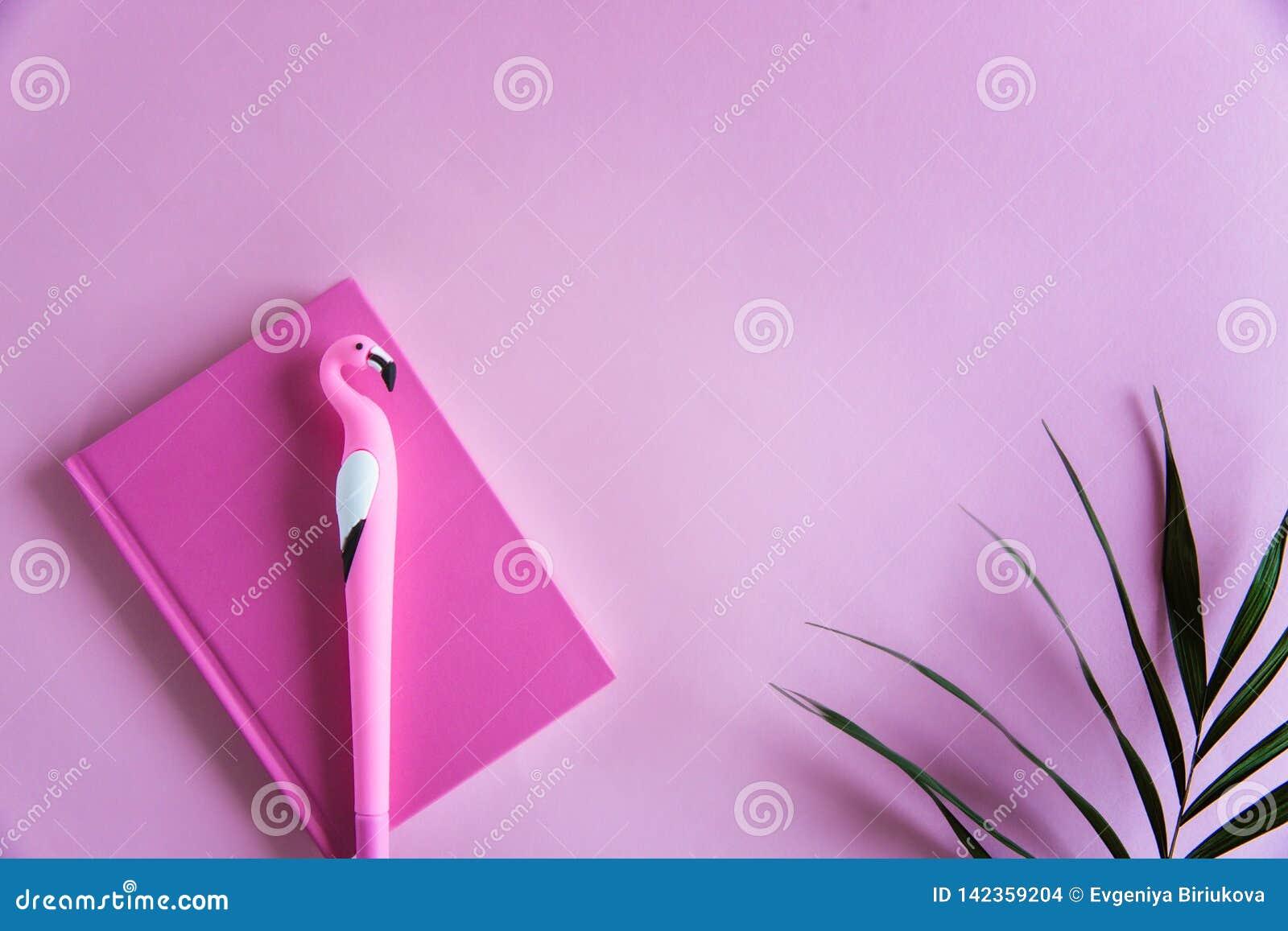 Carnet rose pour les notes, le stylo drôle de flamant et les palmettes vertes sur le fond en pastel rose Configuration plate Vue